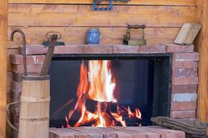 Kaminfeuer umrahmt mit Backsteinen und antiken Objekten