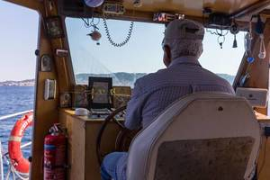 Kapitän am Schiffssteuer auf dem Myrtoischen Meer