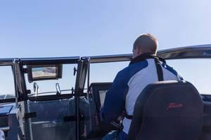 Kapitän steuert ein Yamarin Schnellboot an seinem Display, vor blauem Himmel
