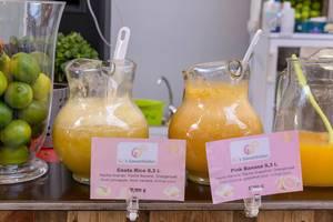 Karaffen mit frisch gepressten Smooties aus verschiedenen Früchten und Glasschale mit Limetten