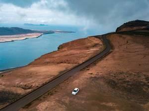 Karge Küstenlandschaft mit einem einzigen weißen Auto. Luftbildaufnahme