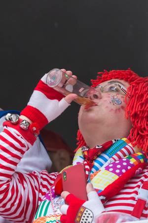 Karneval in Köln: Frau in rot-weißem Kostüm, Handschuhen mit dem Kölner Wappen und roter Perücke trinkt ein Kölsch