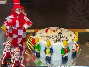 "Karneval in Köln: Torte mit dem Narrenruf ""Kölle Alaaf"" neben Clowns im rot-weiß Kostüm"