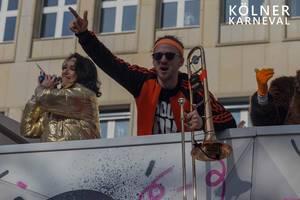 """Karnevalist mit Posaune auf einem Festwagen beim Karnevalsumzug, neben dem Bildtitel """"Kölner Karneval"""""""