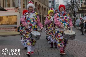 """Karnevalisten laufen in Clownskostüm durch die Fußgängerzone und trommeln neben dem Bildtitel """"Kölner Karneval"""""""