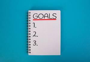 """Karo-Ringblock mit der Aufschrift """"Goals"""" - Ziele -  vor einem blauen Hintergrund"""