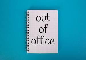 """Karo-Schreibblock mit der Aufschrift """"Out of office"""" - nicht im Amt -  vor einem blauen Hintergrund"""