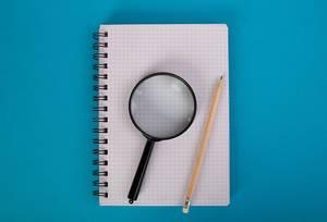 Karokästchen-Schreibblock mit Bleistift und Lupe, vor blauem Hintergrund