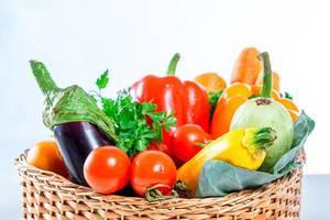 Karotten, Paprika, Balajan-Tomaten,  Zucchini und Petersilie in einem Weidenkorb in der Nahaufnahme
