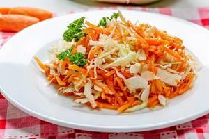 Karotten- und Krautsalat auf weißem Teller in der Nahaufnahme für eine gesunde Ernährung