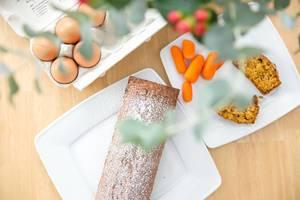 Karottenkuchen, Karotten und Eier mit Blumen im Vordergrund