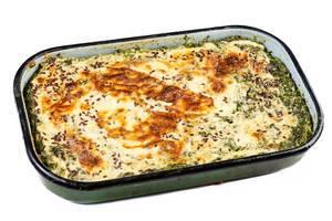 Kartoffel-Spinat-Auflauf mit Käse überbackenen einer grünen Auflaufform, isoliert auf weißem Untergrund