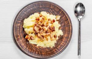 Kartoffelpüree mit gebratenen Zwiebeln und Speck auf einem Teller auf einem weißen Holzhintergrund mit Löffel Top-view