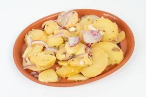 Kartoffelsalat mit geschnittenen Zwiebeln auf einem Teller vor weißem Hintergrund