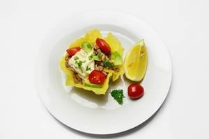 Käsekörbchen gefüllt mit Fleisch, Gemüse, Mayonnaise und Kräutern mit Zitrone auf Teller