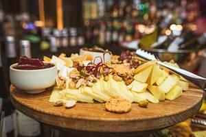 Käseplatte Asorti mit Walnüssen, Marmeladen und grüner Blättern
