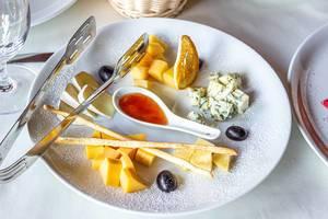 Käseplatte:  Hartkäse, Camembert, Blaushimmelkäse, Brotsticks, Honig und Trauben, auf einem Teller