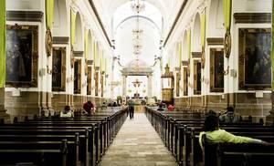 Katholische Kathedrale in Guatemala von innen mit religiösen Bildern, Holzbänken, Altar und einigen Gläubigen