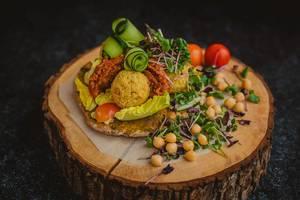 Katsu-Hähnchen-Bällchen garniert mit gekochten Kichererbsen, Kresse, Gurke und rotem Pesto - Nahaufnahme frontal