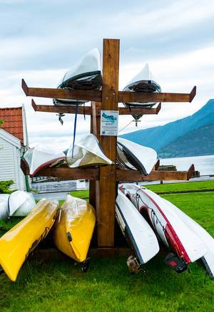 Kayak rental stand with colorful kayaks in the Norwegian countryside (Flip 2019)