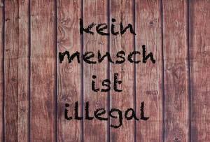 Kein Mensch ist illegal geschrieben auf einer Holzplatte