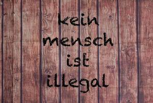 Kein Mensch ist illegal written on a wooden wall