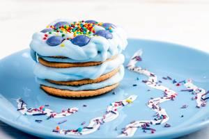 Kekse mit blauer Sahnecreme und bunten Streuseln auf einem verzierten Teller