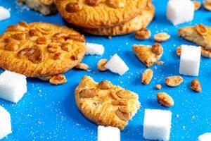 Kekse mit Erdnüssen und Zuckerwürfeln auf blauem Hintergrund Closeup