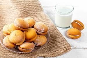 Kekse mit Sahne und Kokos auf einem Holztisch und Leinentuch, neben einem Glas Milch
