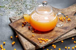 Kettle with fresh sea buckthorn hot drink on a dark background