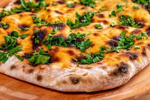 Khachapuri with cheese and herbs on wooden kitchen Board (Flip 2019)