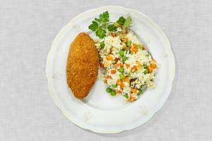 Kiev cutlet with rice and vegetables