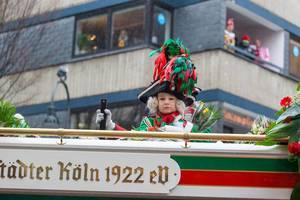 Kind im traditionellen rot-grünem Kostüm mit auffälligem Hut auf dem Wagen vom Traditionskorps des Kölner Karnevals Altstädter Köln 1922 eV.
