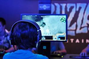 Kind mit leuchtenden Kopfhörern zockt Videospiele