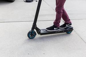 Kind steht auf einem schwarz-blauen Egret One E-Roller auf der E-Cologne Outdoormesse für nachhaltige Mobilität