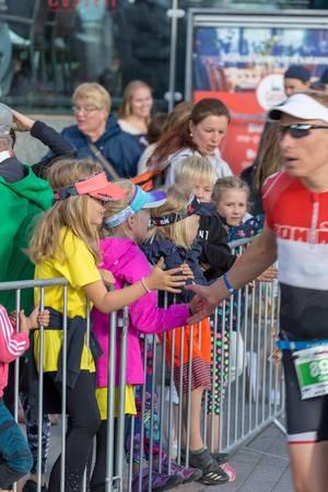 Kinder gratulieren Marathonläufer mit High-Fives kurz vorm Ziel beim Ironman 70.3 Triathlon in Lahti, Finnland