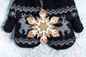 Kinder Handschuhe für den Winter halten eine Holz Schneeflocke vor einem Schnee Hintergrund - Winter Konzept