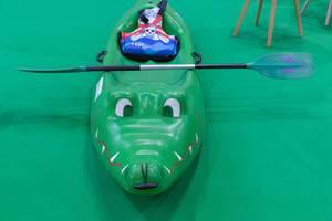 Kinderkanu in Form eines grünen Krokodils mit Paddel und Schwimmweste mit Piratenmotiv