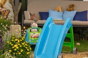 Kinderrutschbahn, Spielzeug und Hollywoodschaukel im Garten