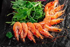 King prawns with fresh arugula leaves on black background (Flip 2019)