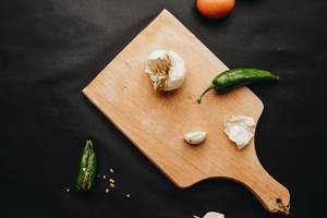 Kitchen flat lay with wooden board, chili peppers and garlic. Dark background