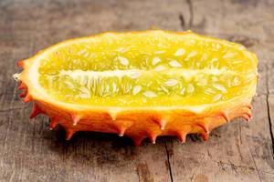 Kiwano fruit half on old wooden background