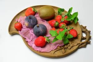 Kiwi mit Feigen und Erdbeeren auf Tonteller mit Pfefferminzblättern garniert