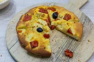 Klassische italienische Focaccia mit Oliven und Tomaten auf einem runden Holzbrett