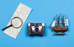 Klassischer Kodak Fotoapparat mit Karte und Schiff auf bleuam Hintergrund