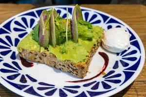 Klassisches Avocado Toast aus Vollkorn mit Avocado, Yuzu & Acai Soße, Pistazien und pochiertem Ei im Flax&Kale Restaurant in Katalonien