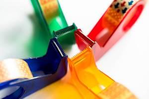 Klebebandabroller verschiedener Farben zeigen Richtung Mitte