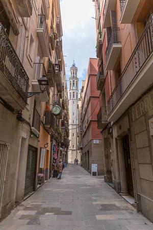 """Kleine Gasse zwischen mediterranen Fassaden mit Blick auf die gotische Kirche """"Basílica de Santa Maria del Mar"""" in Barcelona, Spanien"""