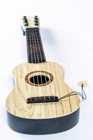 Kleine hölzerne Gitarre mit gespannten Saiten und Gitarrenplättchen vor weißem Hintergrund