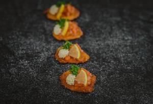 Kleine Kartoffelpuffer garniert mit Kresse, Zitrone, roten Kaviar und Mayonnaise - vertikale Nahaufnahme